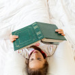 Little smart girl reading big old book in bed — Stock Photo #57599179