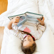 Little girl lying at bed in morning and reading big book — Stock Photo #57599183