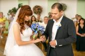 Handsome groom putting wedding ring on brides hand at registry o — Stock Photo