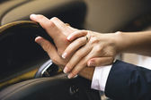 Elegant woman holding hand on men hand while he drives a car — Stock Photo