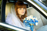 Redhead bride sitting in car and holding blue wedding bouquet — Stock Photo