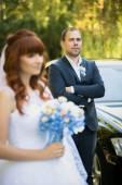 Elegant groom posing with bride against wedding car — Stock Photo