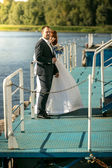 Portrait of bride and groom hugging on pier on river — Stock Photo