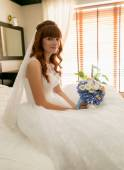 Beautiful redhead bride sitting on bed with bouquet — Стоковое фото