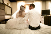 Bride and groom sitting on bed and hugging — Stock Photo
