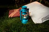 Old oil lamp standing on grass next to pillow and blanket — Zdjęcie stockowe
