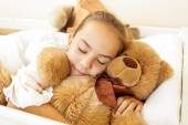 Girl lying on bed with big brown teddy bear — Stock Photo