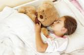 Little brunette girl sleeping in bed with teddy bear — Stock Photo