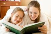 Anne ve kızı yatak, büyük kitap okumak gülümseyen — Stok fotoğraf