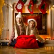 Girls sitting next to fireplace with big red bag for gifts — Stock Photo #57944649