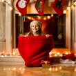 Girl sitting in big red sack at room decorated for Christmas — Stock Photo #57944963