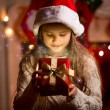 Cute girl looking inside of glowing Christmas present box — Stock Photo #57946753