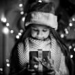 Monochrome portrait of smiling girl opening Christmas present bo — Stock Photo #57946881