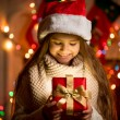 Little girl looking at open box with Christmas present — Stock Photo #57947013