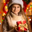 Portrait of beautiful smiling girl holding gift box at Christmas — Stock Photo #57947411