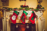 Toned photo of three red Christmas socks hanging on fireplace — Stock Photo
