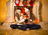 Two sisters sitting next to fireplace with Christmas gifts — Stock Photo