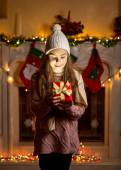 Girl in wool sweater and hat looking inside of glowing present b — Stok fotoğraf