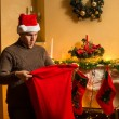 Young man in red hat looking inside of Santa bag with amazement — Stock Photo #57973429