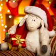 Toy sheep with gift box at decorated for Christmas living room — Stock Photo #57973209