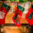 Three christmas stockings hanging on decorated fireplace — Stock Photo #57973995