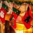 Photo of three red christmas socks hanging on burning fireplace — Stock Photo #57974039