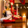 Candles, gift box and woolen sock placed on table against firepl — Stock Photo #57974109