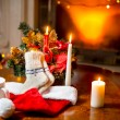 Candles, woolen socks and Santa hat lying on table against  fire — Stock Photo #57974195