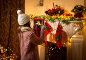 Cute girl making photo of decorated Christmas fireplace on digit — Stock Photo