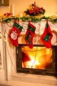 Three Christmas stockings hanging on decorated fireplace — Stock Photo