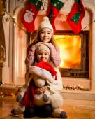 Photo against fireplace of smiling girls sitting on floor with t — Stock Photo
