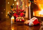 Christmas photo of burning candles with giftbox against fireplac — Stock Photo