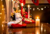 Candles, gift box and woolen sock placed on table against firepl — Stock Photo
