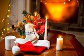 Candles, woolen socks and Santa hat lying on table against  fire — Stok fotoğraf