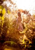 Landscape of meadow at sunny day with woman walking on path — Stok fotoğraf
