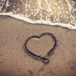 Toned photo of heart drawn on sand sea beach — Stock Photo #58389401