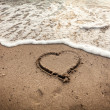 Toned photo of heart drawn on sand being washed by wave — Stock Photo #58389429