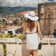 Photo of beautiful woman wearing hat looking at old city — Stock Photo #58389637