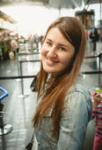 Portrait of smiling brunette woman standing at queue in airport — Stock Photo