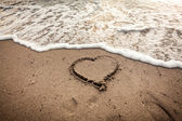 Toned photo of heart drawn on sand being washed by wave — Stock Photo