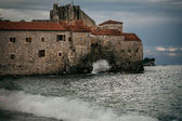 Stone citadel on high cliff at late evening in stormy sea — Stock Photo