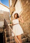Brunette woman posing on old stairway at stone building — Fotografia Stock