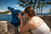 Young woman looking on landscape through touristic telescope — Foto de Stock