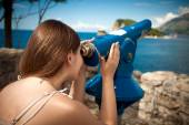 Young woman looking on mountain through touristic telescope — Foto de Stock