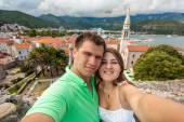 Selfie of young couple in love posing against old city of Budva — Stock Photo