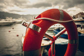 Toned photo of lifebuoy at rainy weather in seaport  — Stock Photo