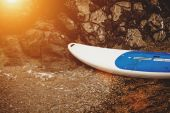 Surfboard lying on sandy beach at sunset rays — Foto de Stock