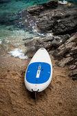 Surfboard lying on sand beach next to wavy sea — Stock Photo