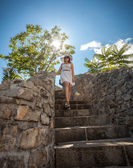 Woman in white hat walking down the stone stairs at sunny day — Stock Photo