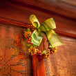 Photo of wooden door decorated with traditional Christmas bow — Stock Photo #58984105